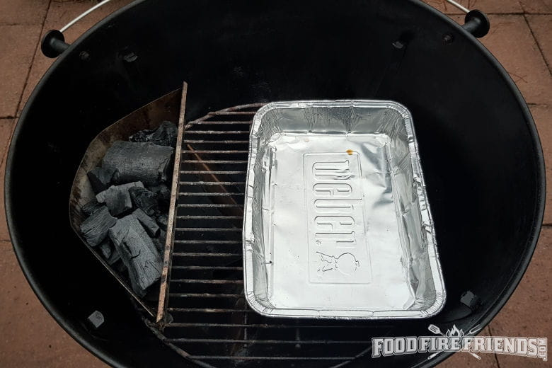 A weber ketttle grill set up for 2-zone grilling