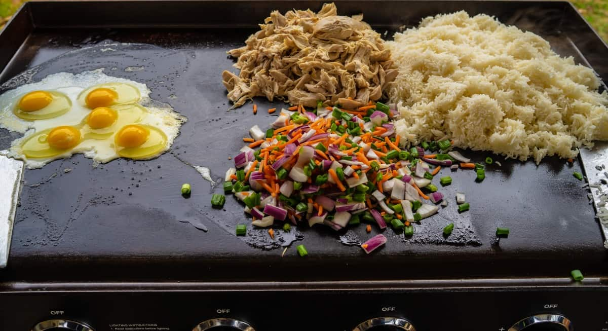 Eggs, diced veg and rice being cooked on a griddle