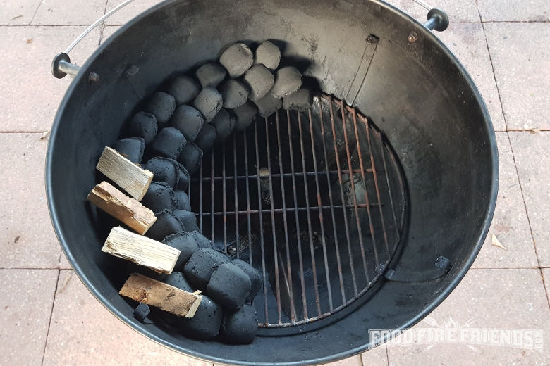 Overhead view of charcoal snake set up in a weber kettle grill with smoking wood on the snake