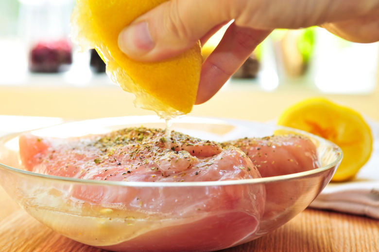A piece of chicken breast being prepared to marinate in herbs and lemon juice