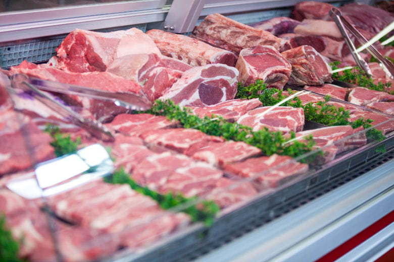 Close up, angled view of portions of meat in a counter
