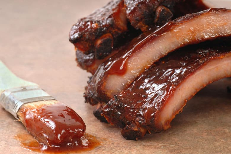 BBQ ribs dripping in thick sauce with a paint brush laying beside them
