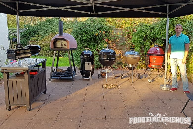 A collection of bbqs and smokers on a tiled patio