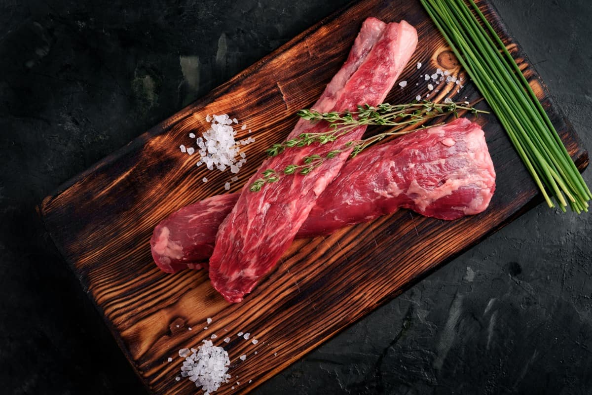 Two beef tenderloin on a cutting board, with sea salt, thyme and unchopped chive stalks