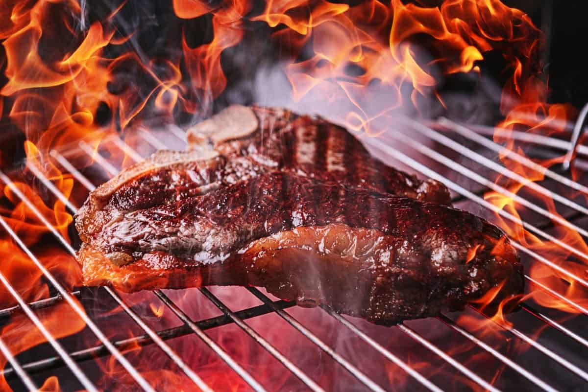 Steak cooking over a charcoal grill fire