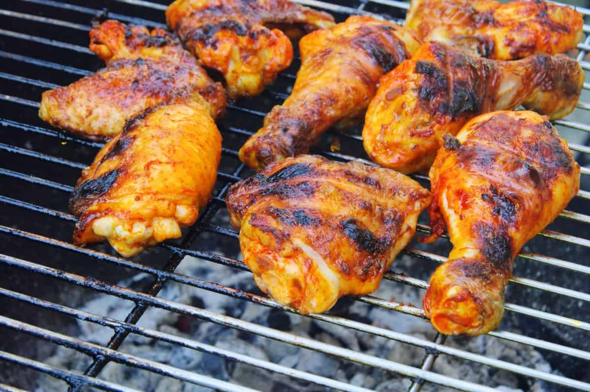 Charred, crispy chicken pieces on a charcoal grill