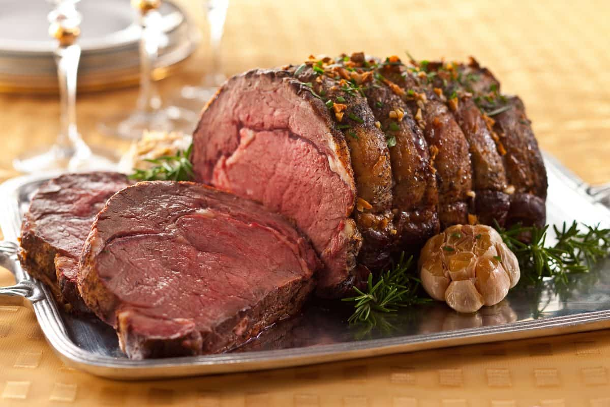 A perfectly medium-rare roasted prime rib on a serving tray