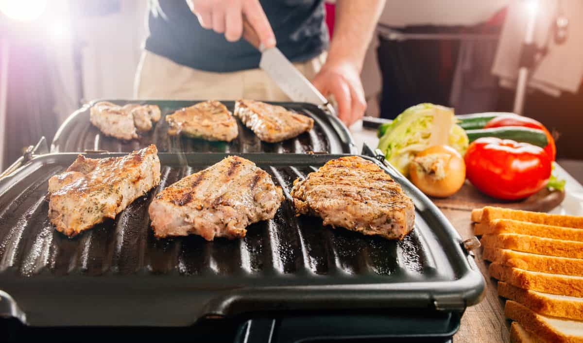 An electric, George Foreman style grill, cooking steaks in a kitchen