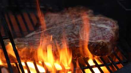 A grill flare up with large flames building under a steak
