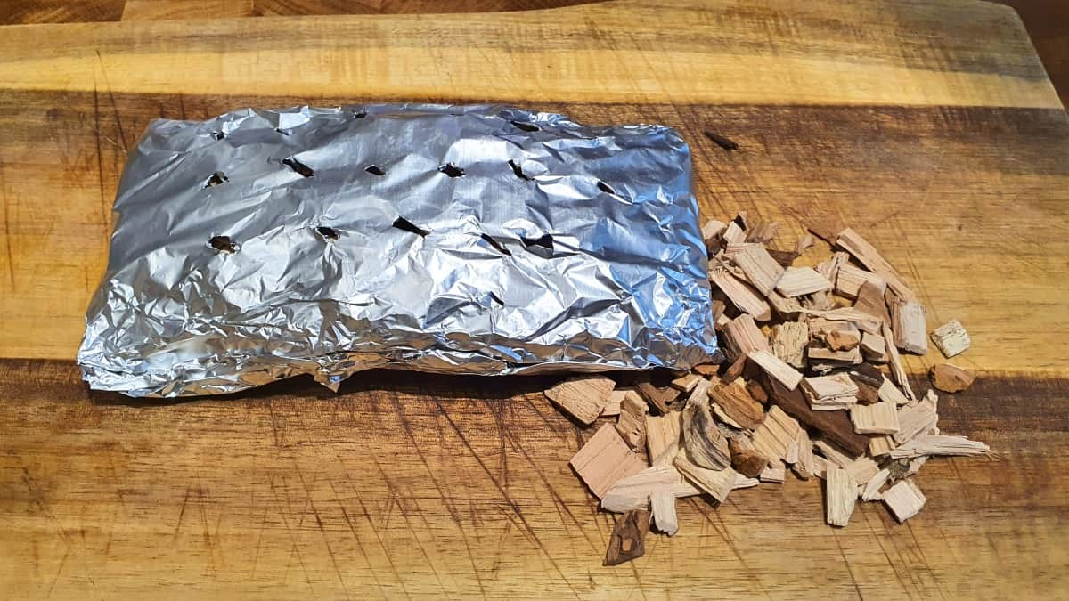 A home made foil packet for smoking wood chips in a grill