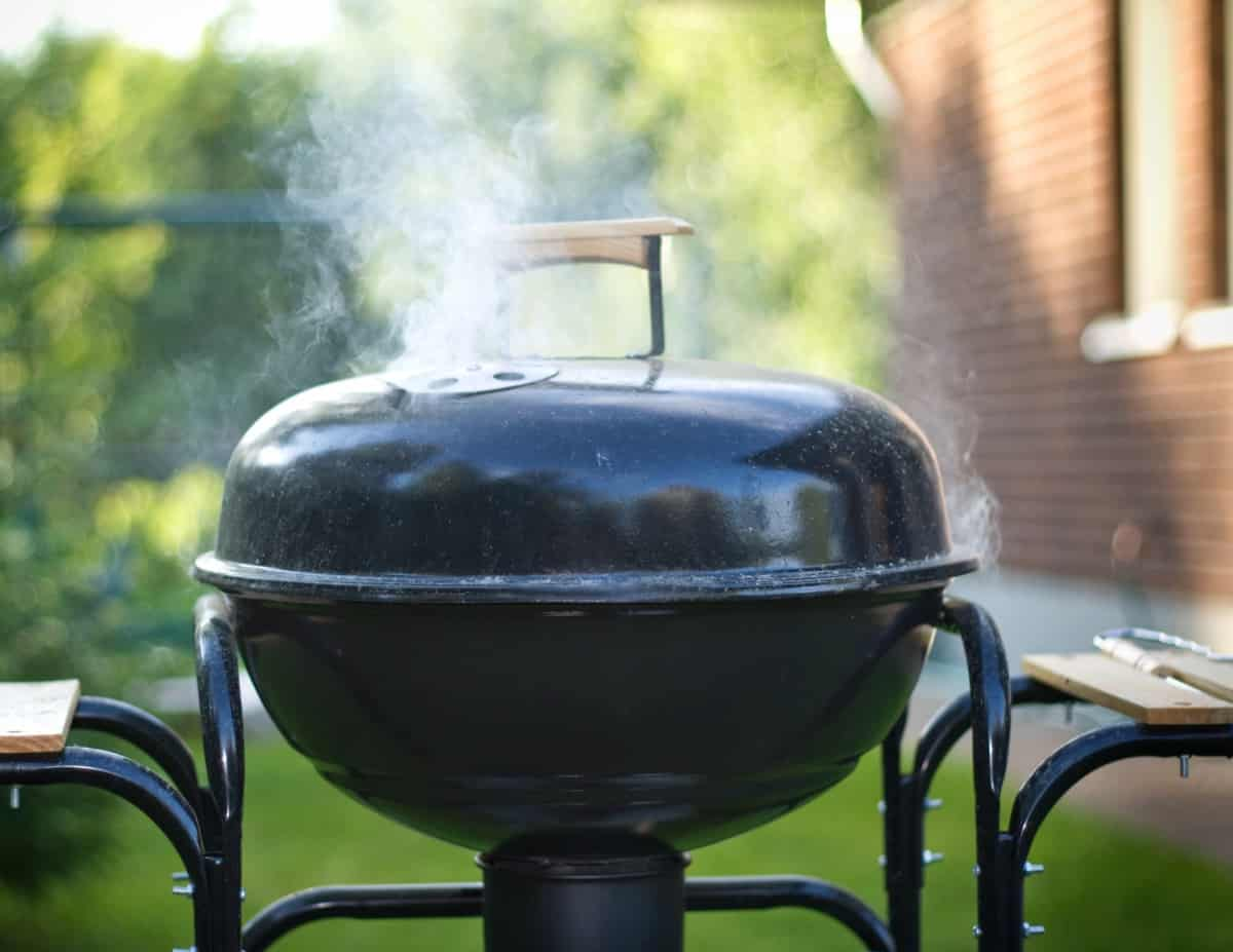 A charcoal grill with smoke coming out of lid