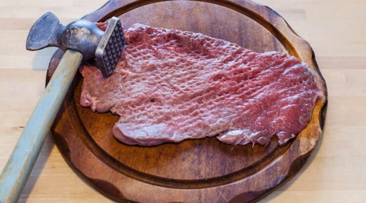 A piece of meat being tenderized by a mallet while on a round chopping board.