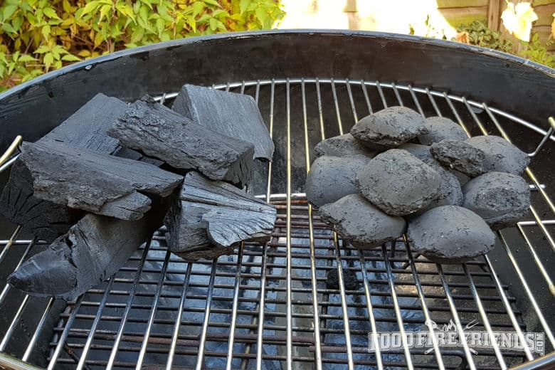 A close up of unlit lump charcoal next to briquettes on a weber grill