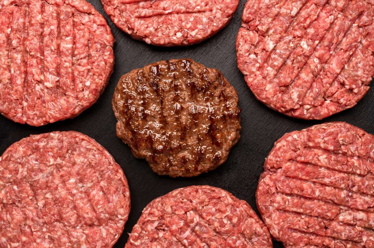 A cooked burger surrounded by raw burgers shot from above