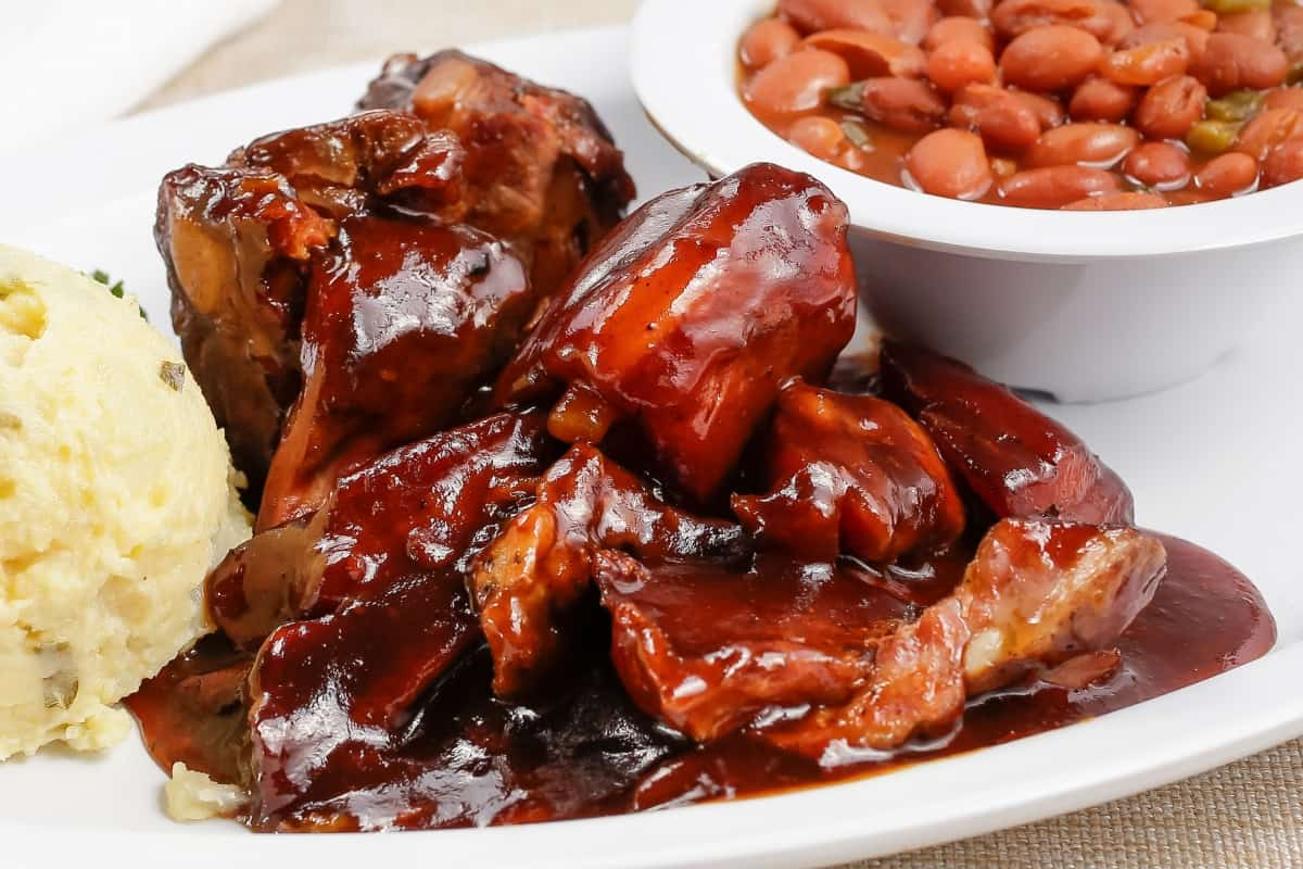rib tips glazed with bbq sauce, on a white plate with mashed potato and some beans