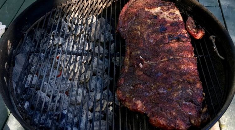 Ribs cooking indirect on a kettle style charcoal grill
