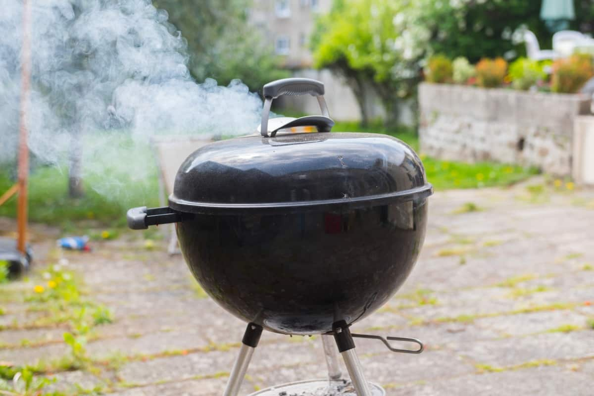 A smoking charcoal kettle grill on a patio