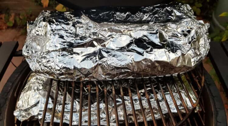 Racks of ribs, wrapped in foil and back on the grill Texas crutch style