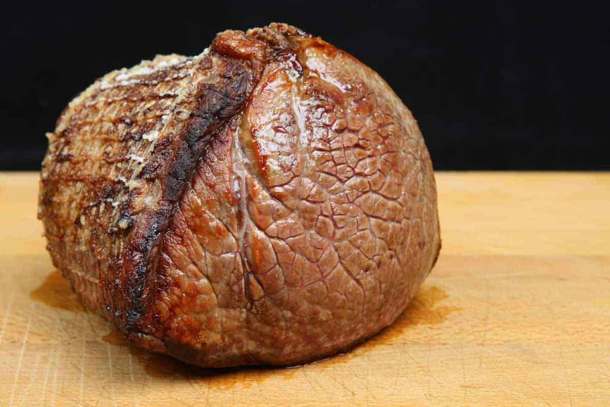 A joint of roast beef resting on a chopping board