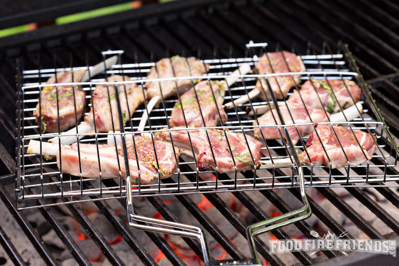 Close up of lamb cutlets in a grill basket over a charcoal grill