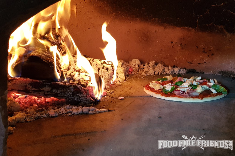 A pizza being cooked in a large wood fired oven