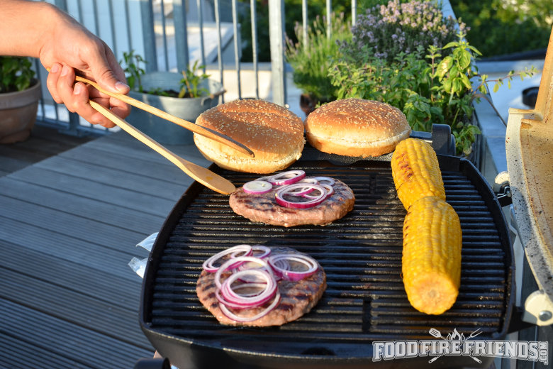 A couple of burgers and corn being grilled on a small grill on a balcony