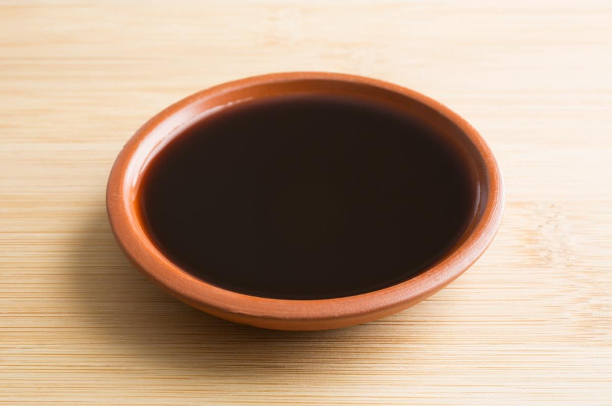 A brown bowl of liquid smoke on a light wood surface