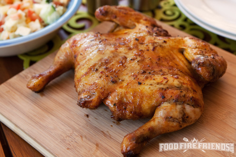 A grilled spatchcock chicken on a woodne chopping board