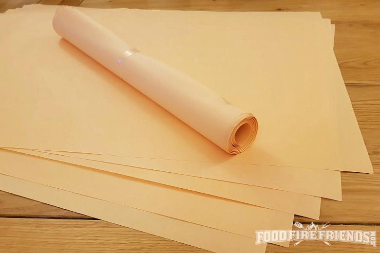 A roll and some sheets of pink butcher paper on a wooden table