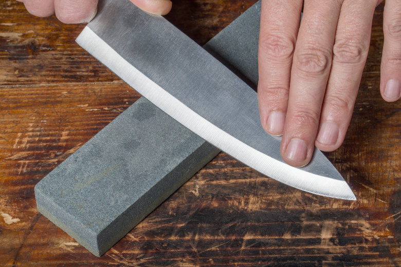 Image of a knife being sharpened on a whetstone
