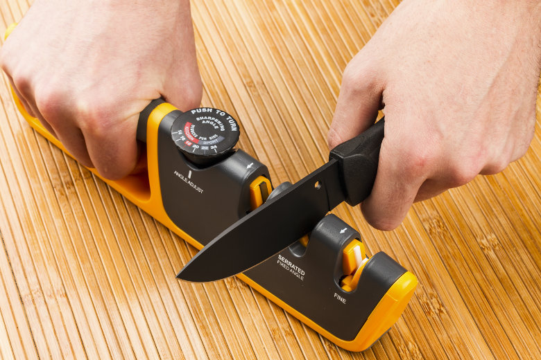 Close up of a man pulling a knife through an adjustable manual knife sharpener