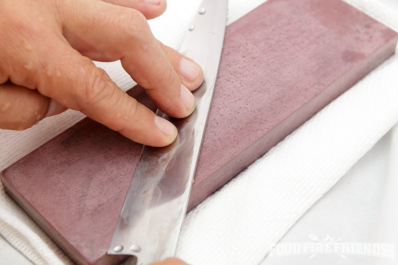 Mans hands sharpening a kitchen knife on a purple whetstone resting on a white towel
