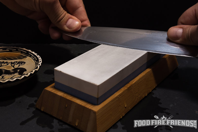 Kicthen knife being sharpened on a whetstone