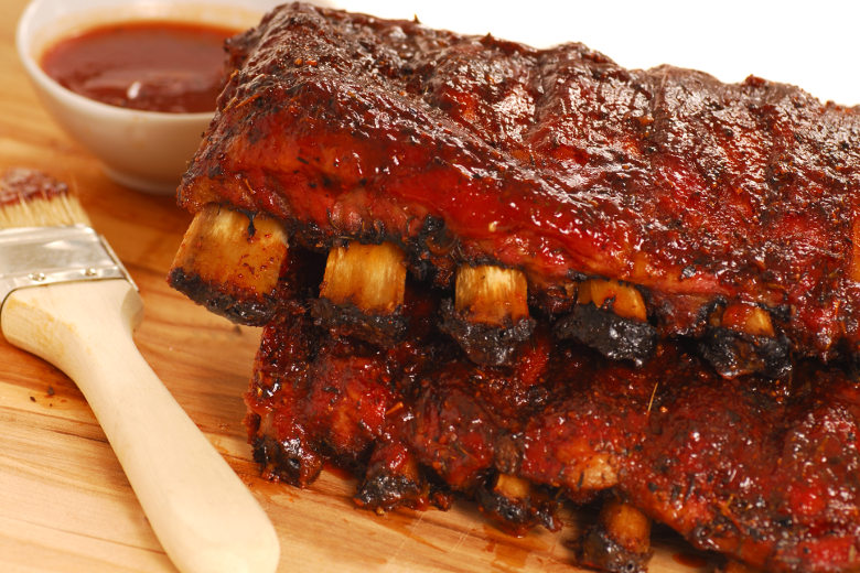 racks of ribs dripping in sauce, with a brush and pot of sauce nearby