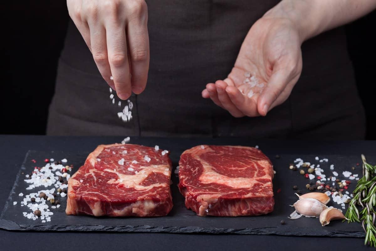 A woman's hands sprinkling salt onto two steaks on a slate surface