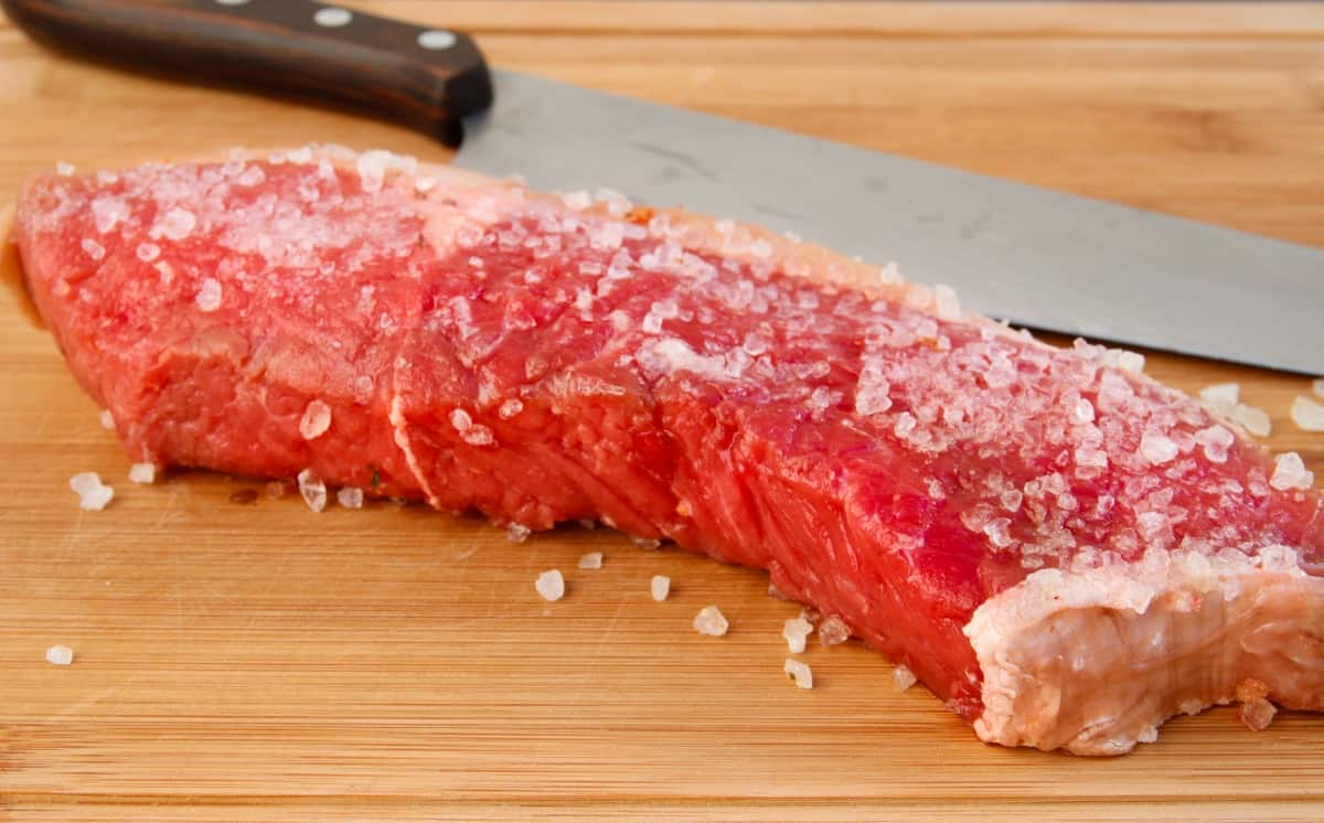 A beef steak coated liberally with coarse salt to dry brine it