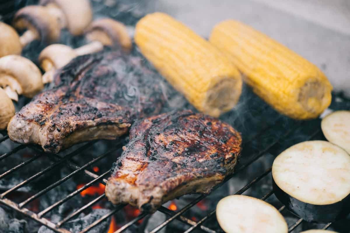 Steaks, corn and mushrooms on a hot grill