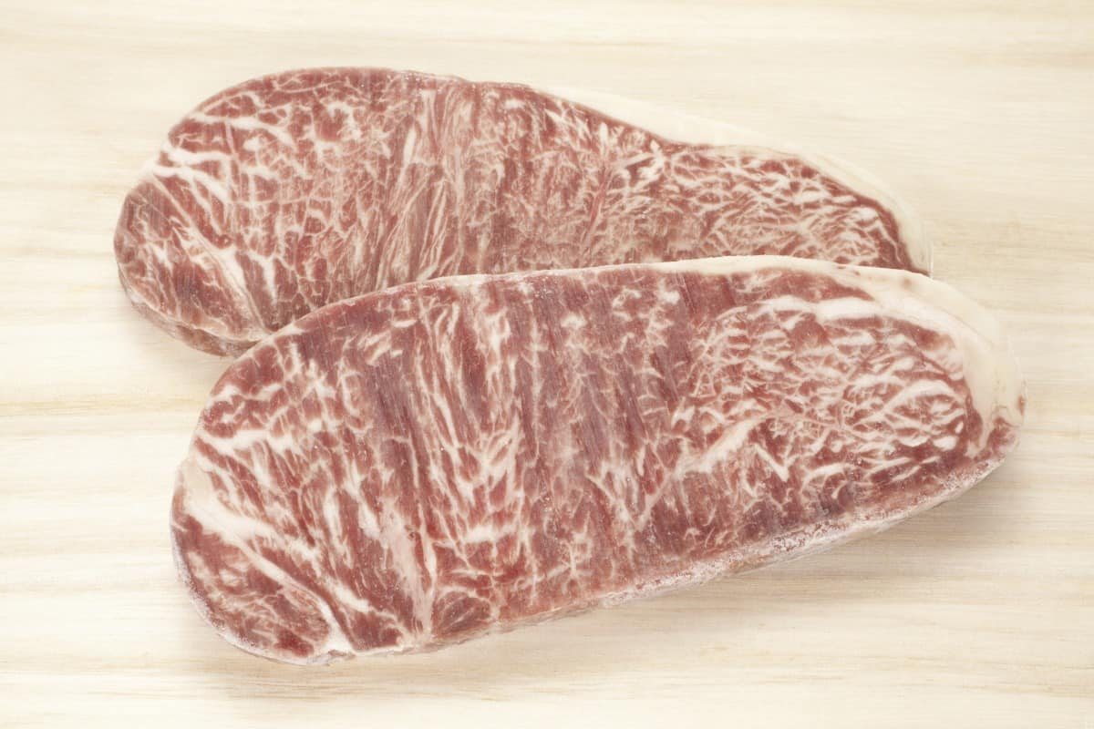Two frozen wagyu steaks on a light colored surface