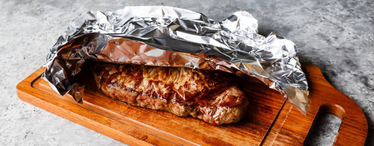 A grilled steak resting on cutting board under loosely tented foil