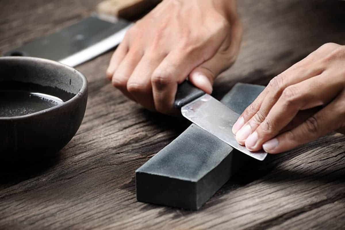 A knife being sharpened on a whetstone next to bowl of water on wooden table
