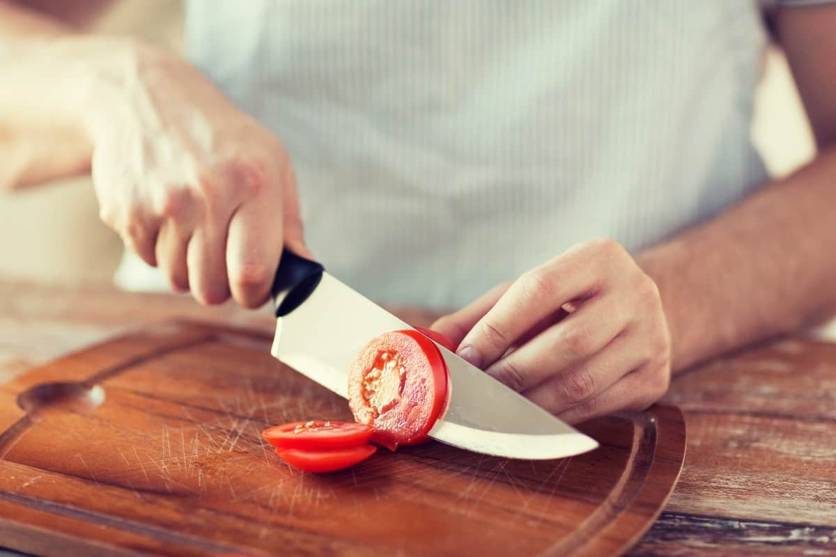 A male chef slicing a tomato with a sharp knife
