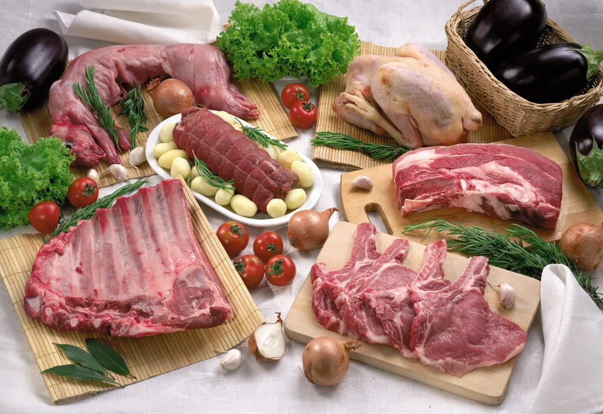 A selecton of raw meat and poultry on cutting boards, with veg on a white background