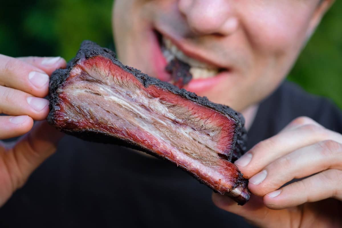 A person taking a bite out of a beef rib with a good smoke ring