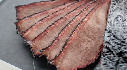 The smoke ring seen in a few slices of smoked brisket fanned out on a chopping board