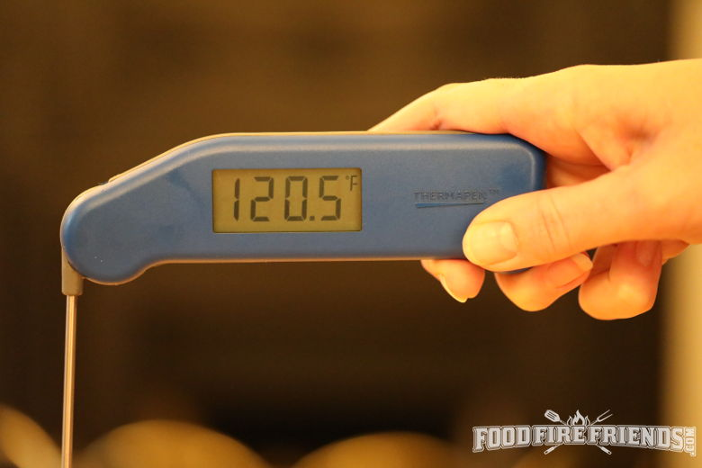 An instant read thermometer showing a reading of 120.5 against a blurred background