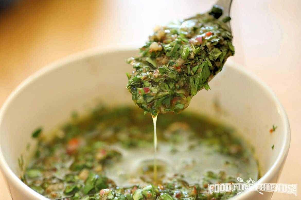 Chimichurri dripping from a spoon into a bowl