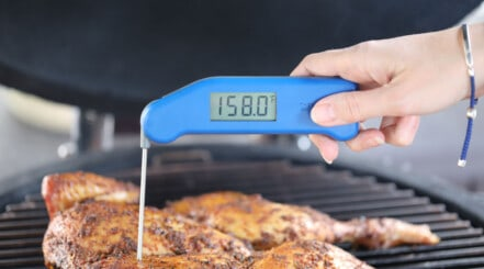 An instant read thermometer being used to take the temp of a spatchcock chicken on a grill
