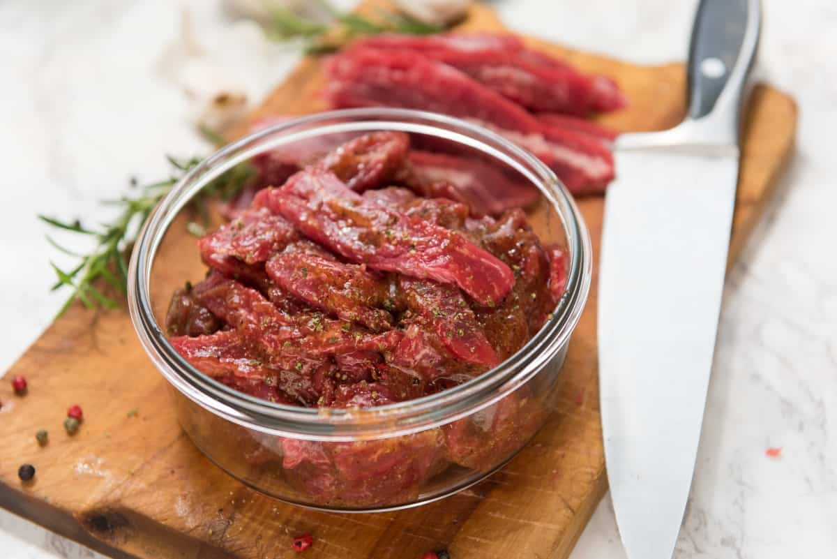 marinating flank steak in a bowl, on cutting board next to a large knife