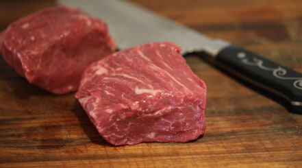 USDA graded fillet steak on a chopping board with a Japanese style knife
