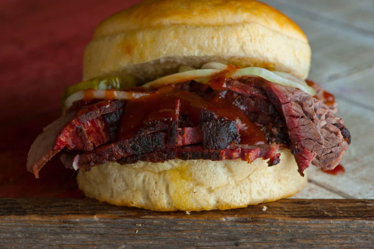 A brisket roll, with sauce and pickles on top of the sliced brisket